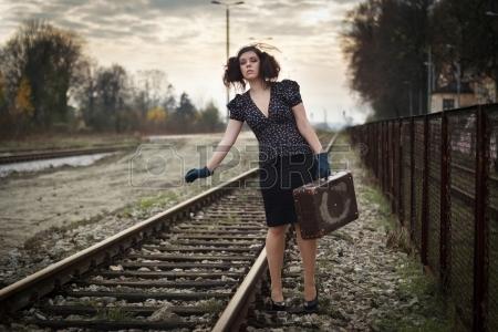 16472424-空の鉄道プラットフォームで電車を待つ少女